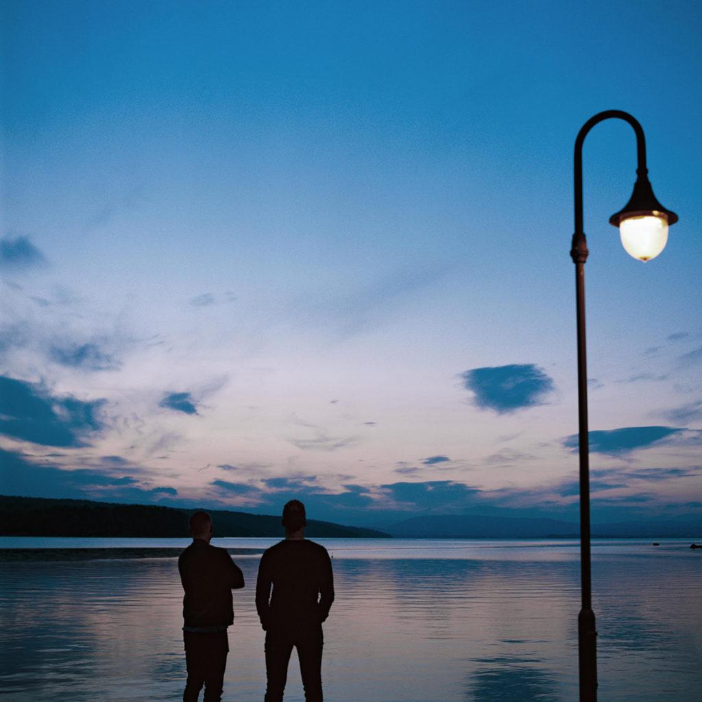 Bilde av Lars Marius og Anders som står og skuer utover sjøen i skumringen.