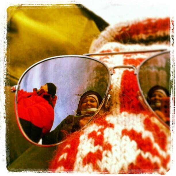 Bilde av solbriller som viser to personer i refleksjonen