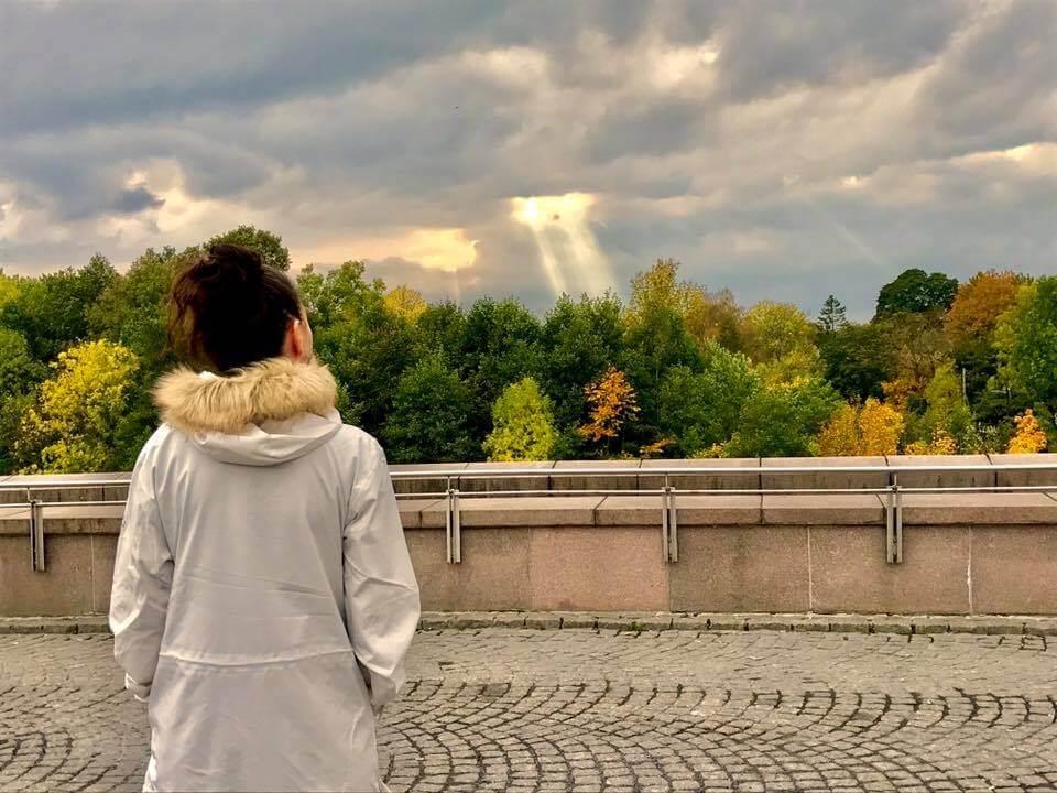 Bilde av Jeanette som ser på solstråler som bryter gjennom himmelen