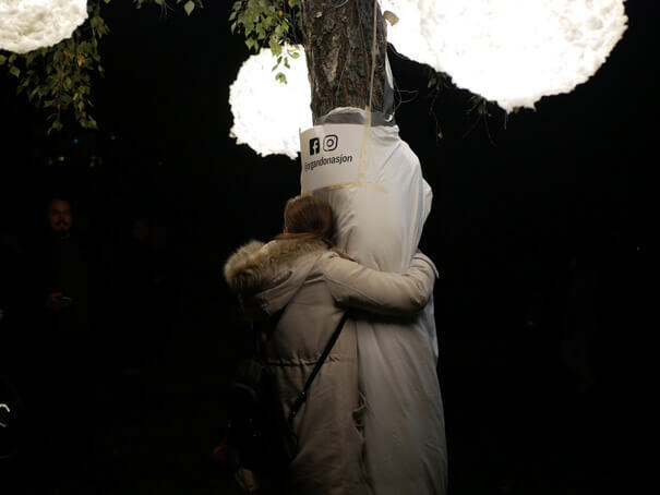 Bilde av en jente som klemmer et tre. I treet henger det store lykter som lyser.