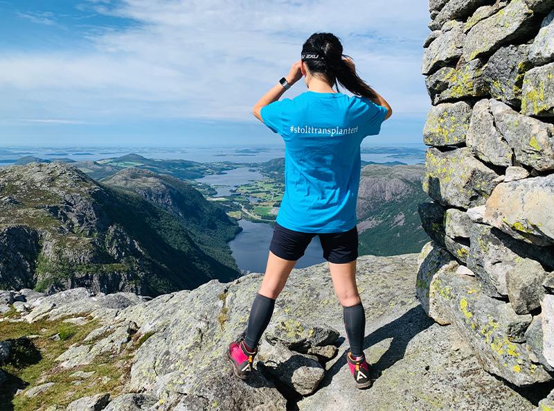 Bildet av Eileen på en fjelltopp som skuer ut over havet. På t-skjorten står det #stolttransplanter