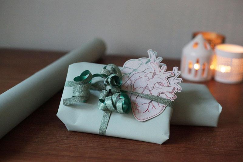 julegave med julekort på bord med stemningsfylte tente lys